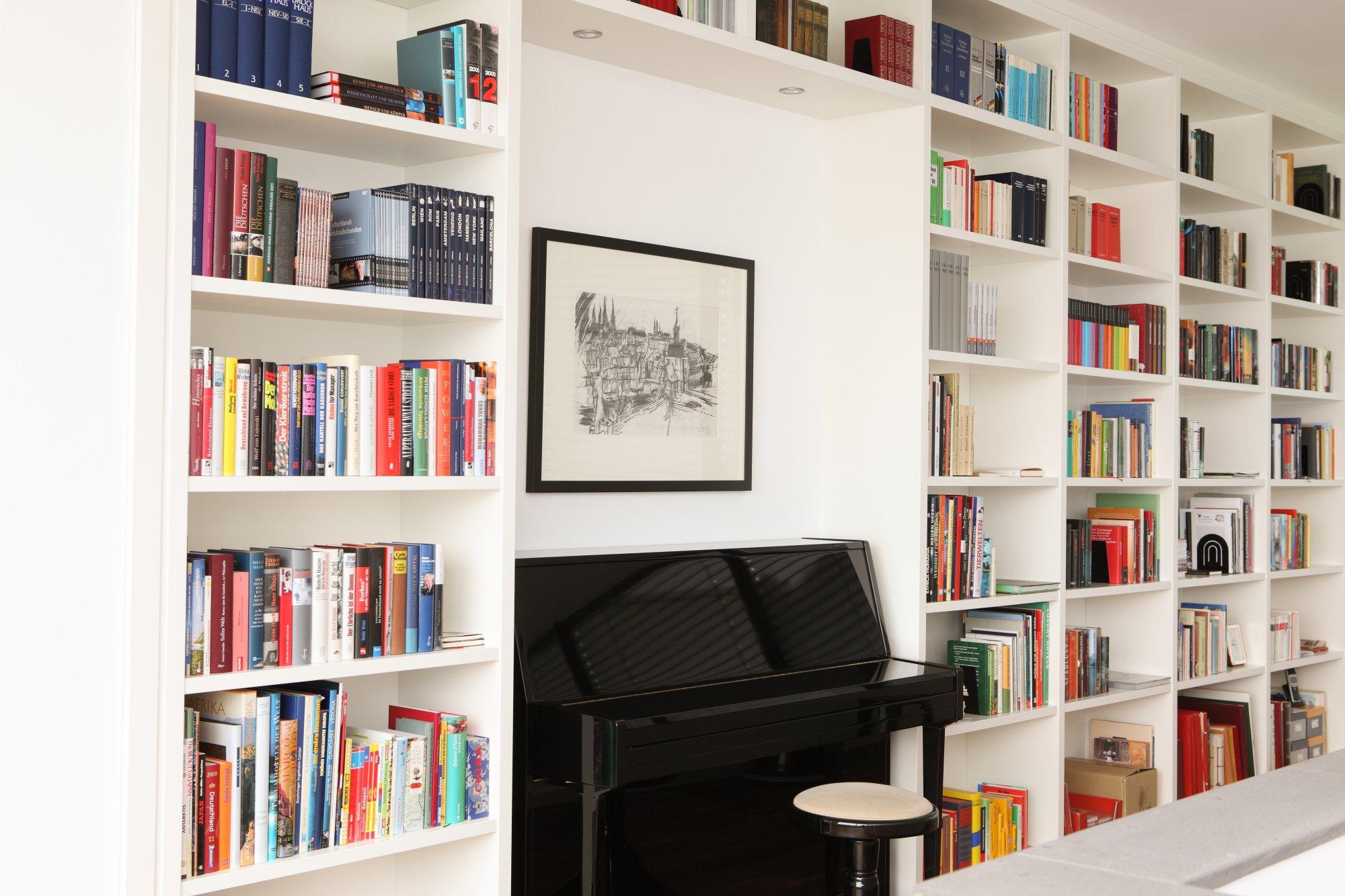 Bücherregalwand in weiß lackiert als Rahmen für Klavier