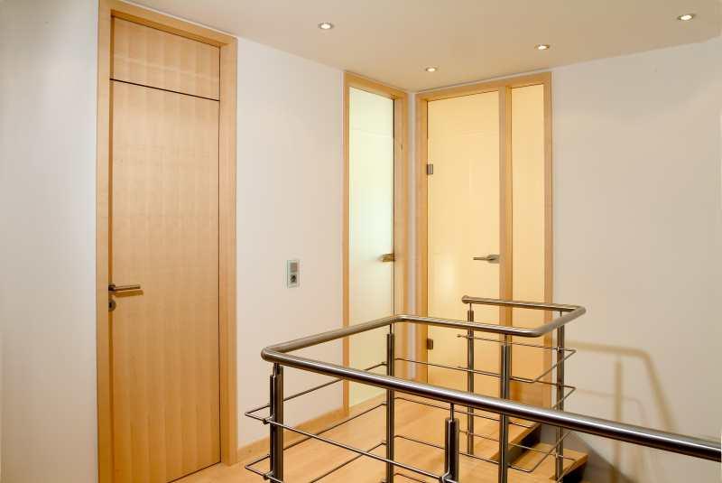 oberes Treppenhauspodest mit raumhohen Zimmertüren in Ahorn und satiniertem Ganzglas