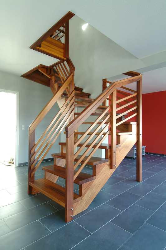 frei im Raum stehende, halbgewendelte Treppe in Merbau Massivholz, beidseitig aufgesattelt mit Geländer und Handlauf